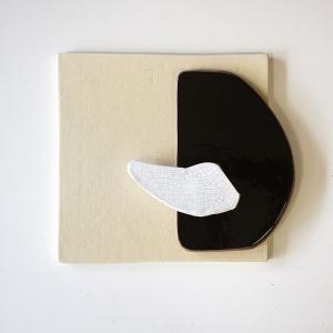 Pieza escultura de cerámica en tres colores: crema en forma de cuadrado, negra en forma de media luna y blanca más pequeña. Para colgar en la pared