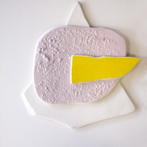 Pieza escultura de cerámica en tres colores para colgar en la pared de 3 colores. 1 blanco en forma de triangulo, sobre este una pieza casi redonda rosa y sobre este, otra pieza más pequeña amarilla.